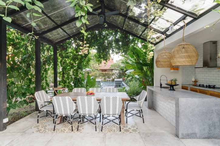 Open, outdoor living space or kitchen with empty dining room table and chairs outside, against green fresh plants on background