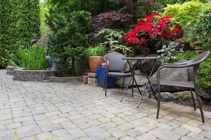 stone paver patio hardscape with wicker bistro furniture chair and table set stock photo